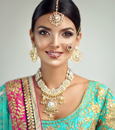 Young attractive woman, dressed in a traditional indian suit-sari, with green blouse and shawl (dupatta) with gilded hand-made decoration. Posh jewelry set is consisting of big earrings, bright necklace, head adornment (tikka) and gold nose ring.