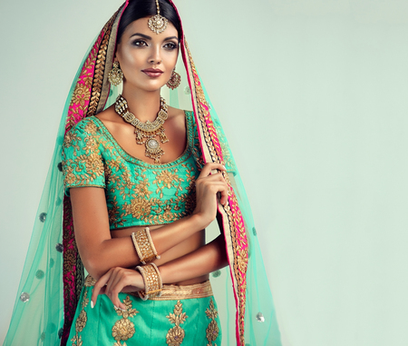 Young attractive woman, dressed in a traditional indian suit-sari, with green blouse and shawl (dupatta) with gilded hand-made decoration. Stock Photo