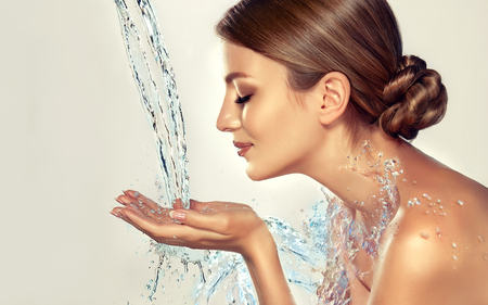 Young, well looking woman, with closed eyes is holding hands under water current. Spurts of pure, fresh, blue water is splashing on graceful hands and body of young attractive woman.  Moisturization (hydration), cosmetology and skin care.