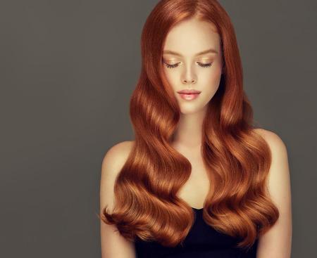 Jong, roodharig mooi model met lang, krullend, goed verzorgd haar. Ierse schoonheid. Uitstekende haargolven. Kapperskunst en haarverzorging. Stockfoto