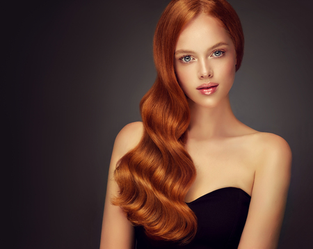 Young, red haired woman  with soft, kind and tender look at viewers. Irish beauty. Excellent hair waves. Hairdressing art and hair care. Hairdressing art, hair care and beauty products.