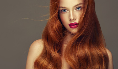 Young, red haired woman with soft, kind and tender look at viewers. Irish beauty. Hairdressing art, hair care and beauty products.