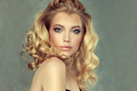 Beautiful model with long, dense, curly hairstyle and vivid makeup. Perfect dense, wavy,and shiny hair. Hairdressing art, hair care and beauty products. Stok Fotoğraf