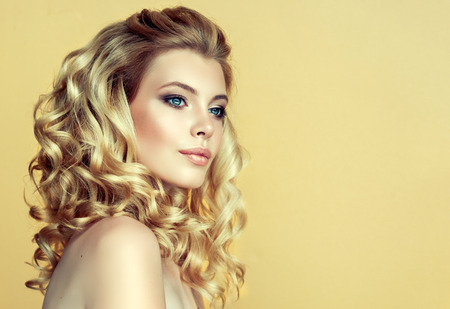 Beautiful model with long, dense, curly hairstyle and vivid makeup. Perfect dense, wavy,and shiny hair. Hairdressing art, hair care and beauty products. Stock Photo