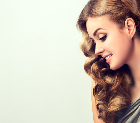 Portrait of young,beautiful, smiling woman with long, dense, wavy brown-golden hair and vivid makeup in profile. Hairdressing and art of makeup.