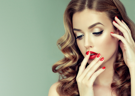 Gilded eyelids, ideal line of eyebrows,lips and nails is colored in bright red and grace in each movement. Portrait of beautiful model with long, dense, wavy brown-golden hair and vivid makeup. Hairdressing, art of makeup and products for beauty.