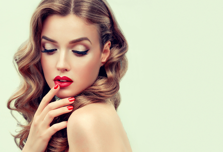 Gilded eyelids, ideal line of eyebrows,lips and nails is colored in bright red and grace in each movement. Portrait of beautiful blue eyed model with long, dense, wavy brown-golden hair and vivid makeup. Hairdressing, art of makeup and products for beauty. Stok Fotoğraf