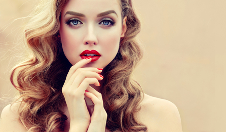 Gilded eyelids, ideal line of eyebrows,lips and nails is colored in bright red and grace in each movement. Portrait of beautiful blue eyed model with long, dense, wavy brown-golden hair and vivid makeup. Hairdressing, art of makeup and products for beauty. 写真素材