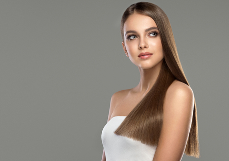 Young and pretty woman with soft smile on the face in demonstrating perfectly looking, dense and straight shiny hair. Natural gloss of healthy hair. Hair care and hairdressing art. Фото со стока