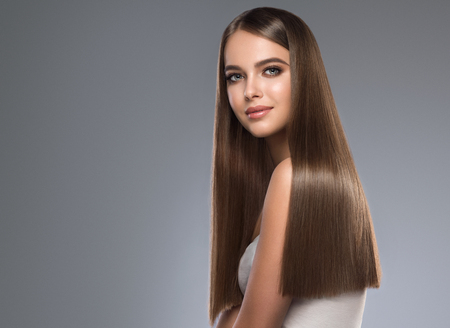 Young, brown haired beautiful model with long,  straight, well groomed hair. Hair care and hairdressing art.