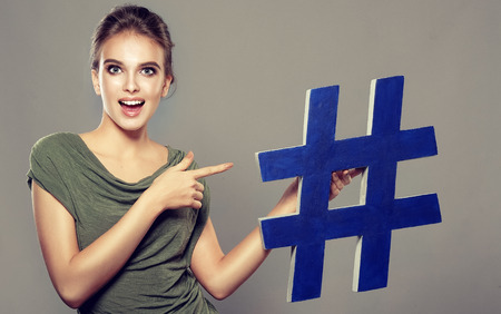 Nice, young woman with wide smile and amazed facial expression is holding big, blue hashtag sign on the hands. Providing of attraction of interest and advancing in social networks.