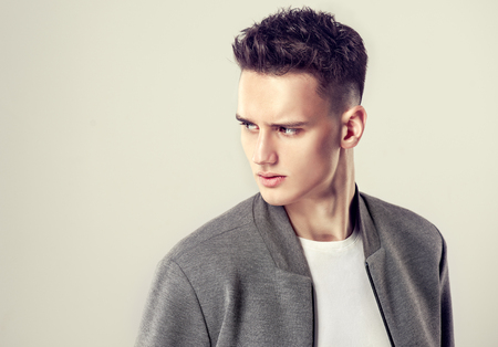 Portrait of attractive mature man dressed in a white t-shirt and grey stylish bomber jacket. Fashionable haircut with the short temples on the head of young handsome male-model. Example of trendy man