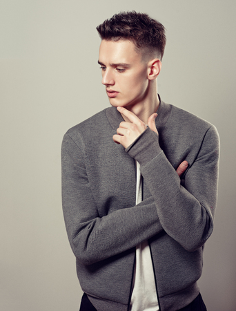 Portrait of attractive mature man dressed in a white t-shirt and grey stylish bomber jacket. Fashionable haircut with the short temples on the head of young handsome male-model. Example of trendy man hairstyle. Hairdressing art.