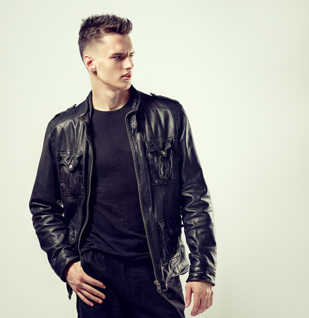 Bold look, dynamic pose and modern, trendy style in black color. Young, handsome man with sporty figure dressed in a black stylish leather jacket, t-shirt and trousers. Fashionable haircut with the short temples on his head.