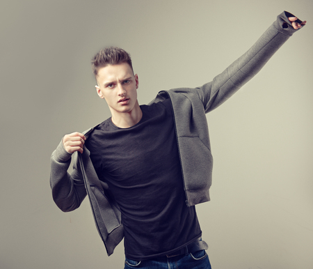 Bold look, dynamic pose and modern, trendy style.Portrait of attractive mature man dressed in a black t-shirt and grey stylish bomber jacket. Fashionable haircut with the short temples on the head of young handsome male-model.