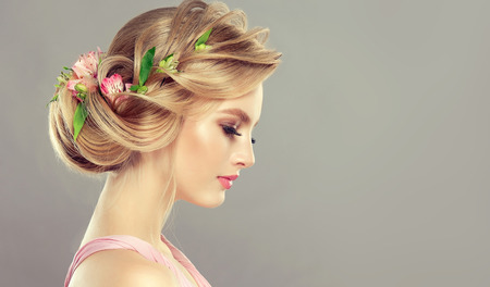 Young, attractive woman is demonstrating blonde hair gathered in elegant evening or wedding hairstyle with fresh flowers in it.  Hairdressing art, coloration of hair and beauty products. Portrait in profile.