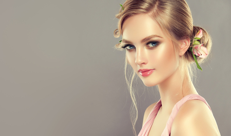 Beautiful woman is demonstrating blonde hair gathered in elegant evening or wedding hairstyle with fresh flowers. Image of spring freshness and blossom of youth. Hairdressing art. Stok Fotoğraf