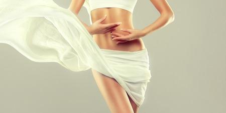 Een deel van het lichaam van een aantrekkelijke vrouw, heupen en slanke, getinte buik, bedekt met zacht, zijden textiel. Sierlijke vrouwenfiguur, als symbool van gezondheid en harmonie.