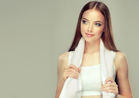 Gorgeous, young woman dressed in a sport top is holding clean ,white towel on the neck. Stock Photo