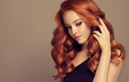 Young, red haired woman is touching tenderly own perfect red hair. Beautiful model with long, dense, curly hairstyle and vivid makeup. Hairdressing art and hair care.
