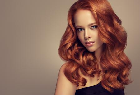 Hermosa modelo joven, pelirroja con cabello largo, rizado y bien peinado. Excelentes ondas capilares. Arte de la peluquería y cuidado del cabello.