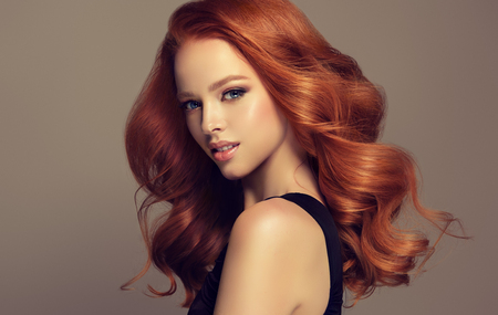Young, red haired woman  with soft, and tender is looking at the viewers. Excellent hair waves. Hairdressing art and hair care.
