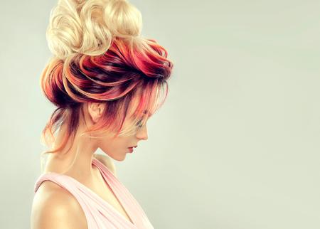 Młoda atrakcyjna kobieta demonstruje wielokolorowe włosy zebrane w elegancką wieczorową lub ślubną fryzurę. Sztuka fryzjerska i koloryzacja włosów. Portret z profilu.