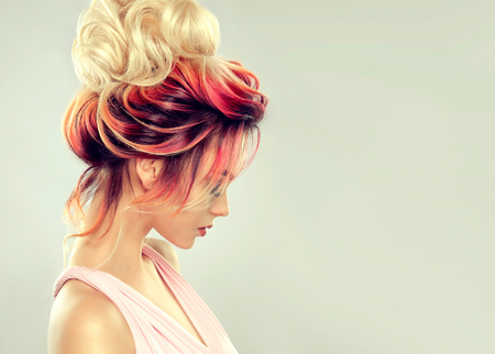 Young attractive woman is demonstrating multi colored hair gathered in elegant evening or wedding hairstyle. Hairdressing art and coloration of hair. Portrait in profile.