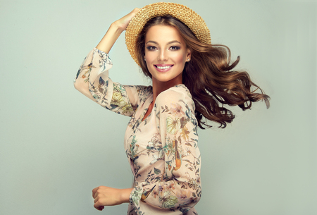 Model dressed in a light printed summer gown and straw hat is showing long, dense, curly hair and vivid makeup. Pure happiness in the sincere smile and flying gesture. Stok Fotoğraf