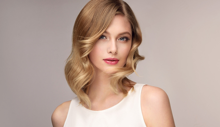 Portret młodej czule uśmiechniętej kobiety o kolorze włosów słomy. Kosmetologia, fryzjerstwo i makijaż.