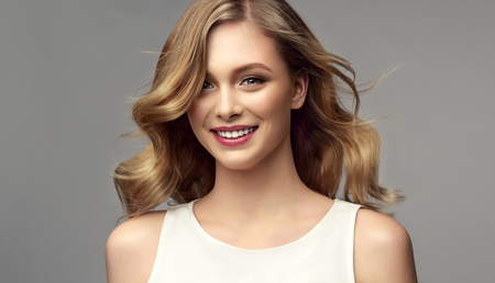 Hair color of straw, middle length hairstyle, soft, almost invisible makeup. Beauty portrait of young, gorgeous woman. Pretty model with wide smile on the face is demonstrating perfectly looking, straight shiny hair.