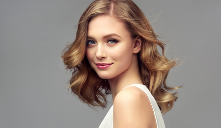 Hair color of straw, middle length hairstyle, soft, almost invisible makeup.  Pretty model with tender smile on the face is demonstrating perfectly looking, straight shiny hair.