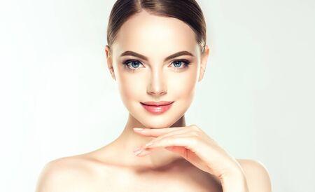 De schitterende, jonge vrouw met schone, verse huid raakt eigen gezicht. Zachte make-up en een lichte glimlach op het perfecte gezicht. Gezichtsbehandeling. Stockfoto