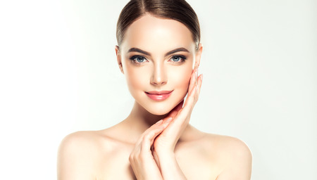 Gorgeous, young woman with clean, fresh skin is touching own face. Soft make up and light smile on the perfect face.Facial treatment. Stock Photo