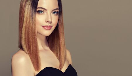 Young and pretty woman with soft smile on the face in demonstrating perfectly looking, middle length straight, shiny hair. Trendy hairstyle. Hair care and hairdressing art. Stockfoto