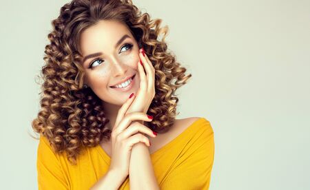 Young, beautiful woman with dense curly hairstyles and freckles on the cheeks is happily looking aside.  Look full of dreams and hopes.