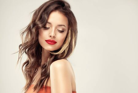 Pretty model with tender smile is demonstrating bright sensual makeup, gilded eyelids and red lipstick. Cosmetology, hairdressing and makeup.