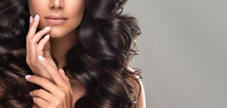 Brown haired woman  with voluminous hair is touching tenderly own face. Beautiful model with long, dense, curly hairstyle and vivid makeup. Stok Fotoğraf
