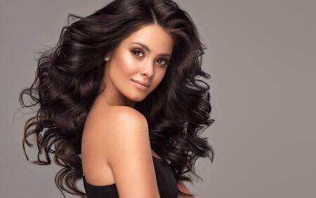 Młoda, brązowowłosa kobieta z obszernymi włosami. Piękna modelka o długiej, gęstej, kręconej fryzurze i żywym makijażu. Idealnie gęste, falowane i lśniące włosy. Sztuka fryzjerska.