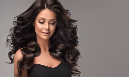 Young, brown haired woman  with voluminous hair.Beautiful model with long, dense, curly hairstyle and vivid makeup. Perfect dense, wavy,and shiny hair. Hairdressing art. Stok Fotoğraf