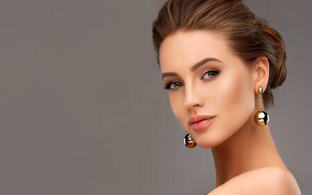 Portrait de belle femme avec un regard brumeux. Lèvres mûres, peintes en rose, longs cils noirs et paupières dorées. Maquillage et cosmétique.