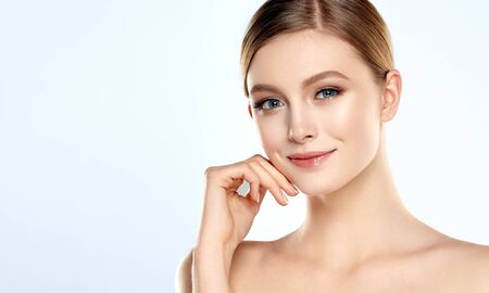Gorgeous, young woman dressed in a soft, elegant makeup is touching the face by graceful fingers.