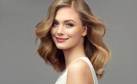 Model met donkerblond haar. Kroeshaar, elegant kapsel omringt het mooie gezicht van een teder lachende jonge vrouw. Haarverzorging en kapperskunst.