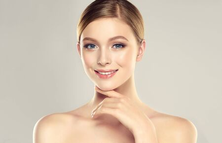 Gorgeous, young woman dressed in a soft, elegant makeup is touching the face by graceful fingers.  Slender neck, bare silky shoulders and elegant gesture of hand. Reklamní fotografie