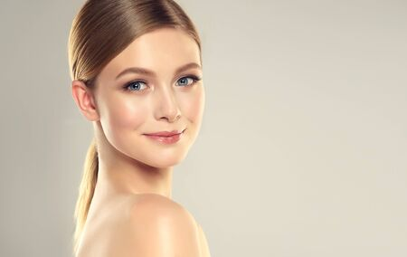 Gorgeous, young woman in elegant makeup is looking on viewers with tender smile on the lips. Beauty and cosmetology. Reklamní fotografie