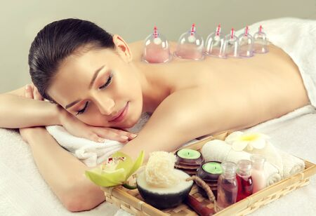 Young attractive woman is undergoing of  vacuum therapy. Young lady is laying on massage table and getting massage treatment. Spa and body massage, recuperation and traditional healthcare methods.