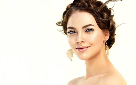 Portrait of woman dressed in splendid evening makeup. Nice looking evening hairdress with braid wrapped around the head and golden earrings in her ears. Playful look with smile.