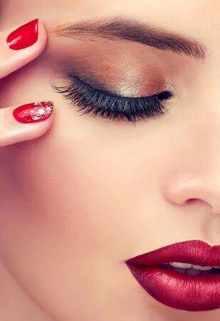 Close-up detail of woman face is reveals closed eye covered by eyelid colored in a smoky makeup,well shaped eyebrow and bright red lips. Makeup, manicure and cosmetic products. Reklamní fotografie