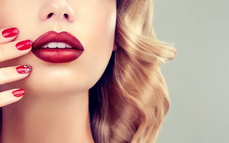 Tender tips of woman fingers is touching ripe lips. Everything in red. Close-up detail of woman face.Makeup, manicure and cosmetic products.