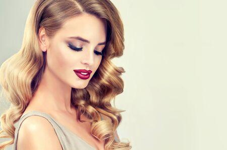 Schönes Model mit langem, dichtem, lockigem Haar und lebendigem Make-up mit rotem Lippenstift. Friseurkunst, Haarpflege und Schönheitsprodukte.